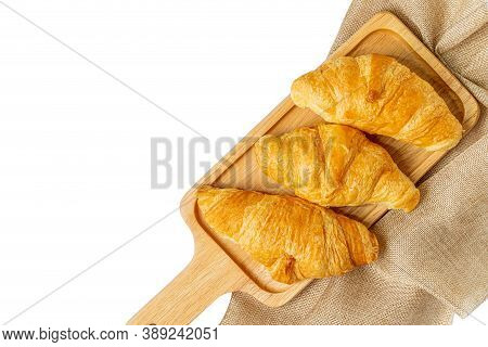 Croissants On Wooden Bread Cutting Board With Sackcloth. Croissant French Breakfast Over White Backg