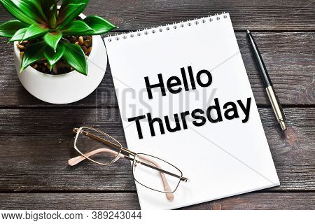 Hello Thursday. The Expression Is Written In Black In A Notebook Near A Pen, Glasses And A Green Pla