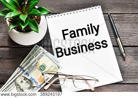 Family Business. Family Business Written In A White Notepad Near A Pen And A Green Plant, Usa Money