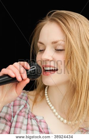 Woman singing while closing her eyes against black background