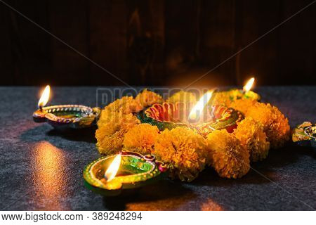 Top View Overhead Clay Lit Light A Fire Already On Diya Or Oil Lamp And Flower, Studio Shot On Concr
