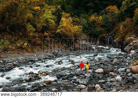 Active Rest On The Nature. A Couple Of Tourists Walking Along A Mountain River In Autumn. An Active