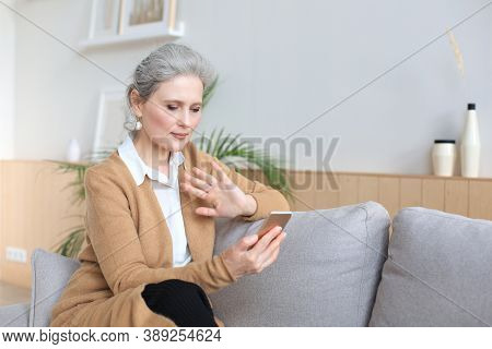 Smiling Middle Aged Woman Holding Phone, Using Mobile Device Apps, Looking At Screen, While Sitting