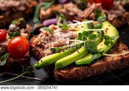 Closeup Of A Tuna Melt Topped With Avocado And Microgreen, On Wholemeal Bread. Italian Cuisine, Deli