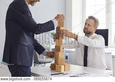 Serious Entrepreneurs Of Different Ages Building Tower Together As Metaphor For Business Succession