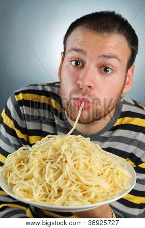 funny young man eating pasta
