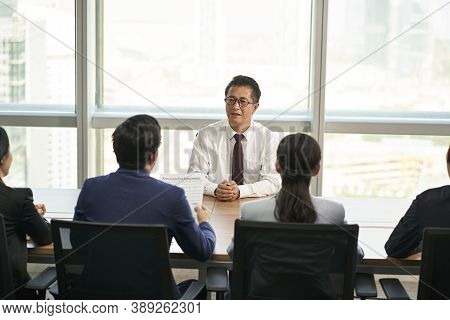 Older Asian Business Man Job Seeker Being Interviewed By A Group Of Young Human Resources Executives