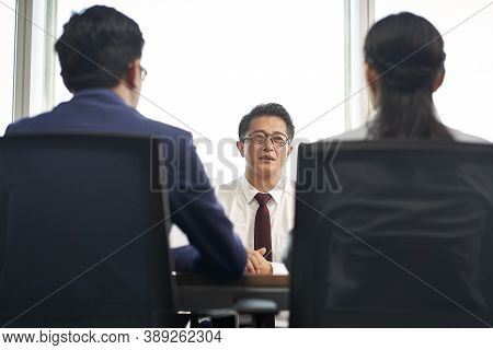 Older Asian Business Man Job Seeker Being Interviewed By Young Human Resources Executives