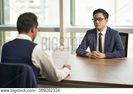 Young Asian Man Being Interviewed By Corporate Human Resources Manager