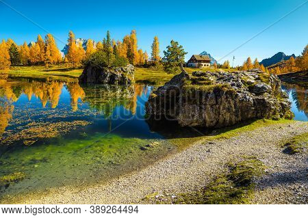 Amazing Colorful Autumn Forest With Spectacular Alpine Lake. Colorful Larches And Small Cute House O