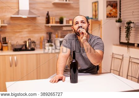 Man In Solitude And Frustration Drinking A Bottle Of Wine Getting Hangover. Unhappy Person Disease A