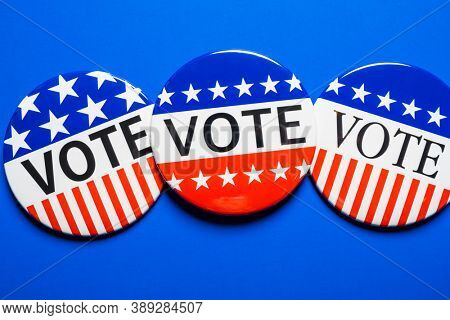 A group of red, white and blue VOTE button on a blue background