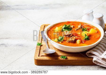 Soup With Beef And Vegetables In A White Plate On A Wooden Board. Traditional Meat Shurpa Soup With