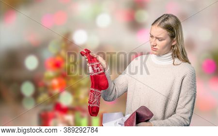 A Disappointing Christmas Present For A Young Woman In Front Of Blurry Christmas Background