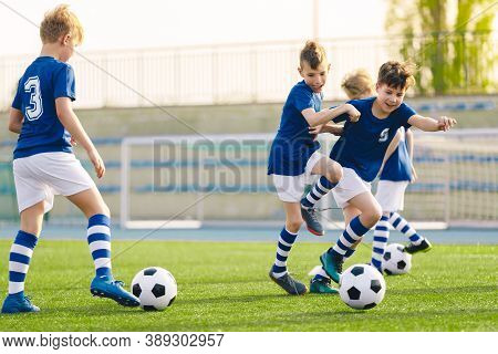 Young Boys Playing Football Training Game. Happy Children Kicking Soccer Balls On Practice Pitch. So