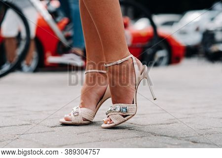 A Woman In High-heeled Shoes With Artificial Diamonds In The City. Beautiful Feet In Shoes Close-up.