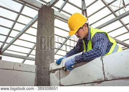 Bricklayer Builder Working With Autoclaved Aerated Concrete Blocks. Walling, Installing Bricks In Co