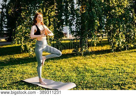Attractive Red-haired Young Woman With Closed Eyes Standing In The Pose Of Vrikshasana Tree Outside