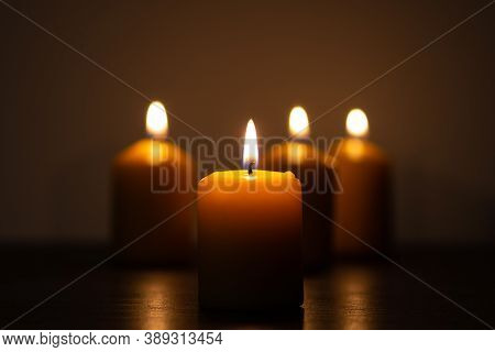 Group Of Lit Candles Burning In The Darkness In Golden Tones With Selective Focus On Candle And Back