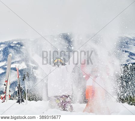 Two Skiers Throwing Fresh Powder Snow High In The Air. Man And Woman Having Fun At Ski Resort With B