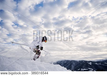Side View Of Male Skier Riding Down Snow-covered Slopes On Skis Under Beautiful Cloudy Sky. Man Free