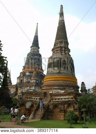 Ayutthaya, Thailand, January 24, 2013: A Group Of Tourists Are Photographed Under Two Stupas In Ayut