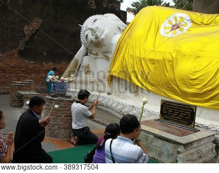 Ayutthaya, Thailand, January 24, 2013: Several Worshipers Pray Before The Reclining Buddha In Ayutth