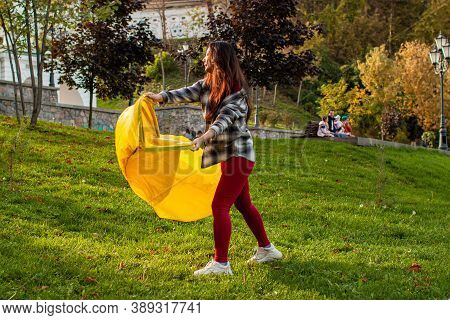 A Young Woman Inflates A Yellow Lamzac With Air. A Woman Inflates An Air Sofa In Park.