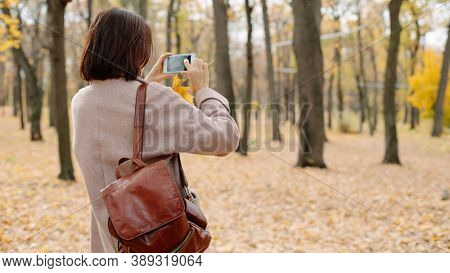 woman taking photo in autumn park, back view