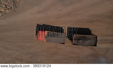 Topview Of Orange Cargo Truck. The Lorry Is Full Of Coal. Sandy Ground And Heap Of Stones On The Bac
