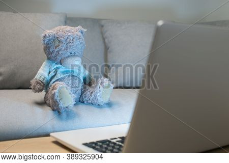 Bangkok / Thailand - October 12 2020 : Teddy Bears Wearing Blue Sweater Using The Laptop In The Livi