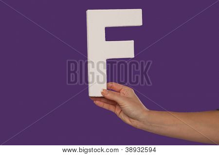 Female hand holding up the uppercase capital letter F isolated against a purple background conceptual of the alphabet, writing, literature and typeface