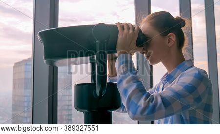 Woman In Plaid Shirt Looking Through Tourist Telescope From Skyscraper, Exploring Cityscape. Summer