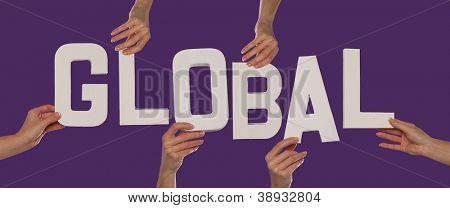 White alphabet lettering spelling GLOBAL held up over a purple studio background by outstreched female hands