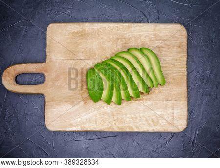 Raw Cut Sliced Avocado On Concrete Background. Freshly Avocado Slices On Wooden Cutting Board. Fresh