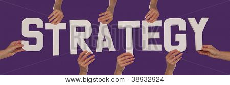 White alphabet lettering spelling STRATEGY held up over a purple studio background by outstreched female hands