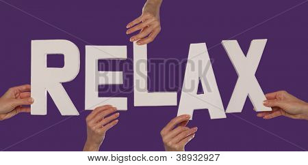 White alphabet lettering spelling RELAX held up over a purple studio background by outstreched female hands