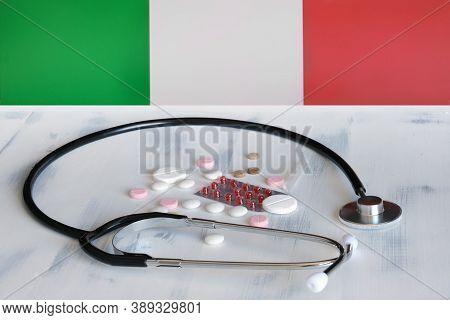 Italian Flag On A Background Of Pills And A Stethoscope On The Table. Italy Flag And Medical Supplie