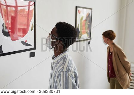 Portrait Of Two Young People Looking At Paintings While Wearing Masks At Modern Art Gallery Exhibiti
