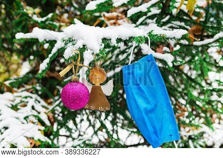 A Branch Of A Christmas Tree In A Winter Forest Is Decorated With Christmas Decorations And A Protec