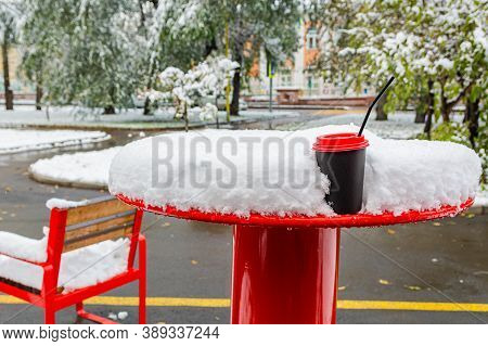 In The Street Cafe In Winter, The Tables Are Covered With Snow. A Paper Cup Of Coffee Is On A Table