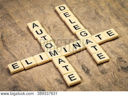 business productivity and lifestyle concept: eliminate, automate and delegate, crossword in ivory letters against textured bark paper