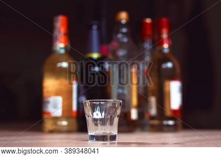 Empty Small Shots Glass In Front Of Multiple Blurry Different Strong Spirits Alcohol Bottles