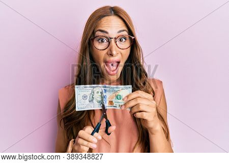Young brunette woman cutting dollars with scissors for currency devaluation celebrating crazy and amazed for success with open eyes screaming excited.