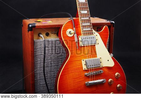 Amplifier For Electric Guitar With Guitar On The Black Background.