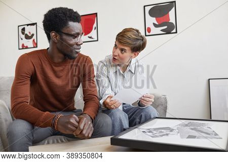 Portrait Of African-american Man Talking To Female Art Gallery Manager While Discussing Paintings An
