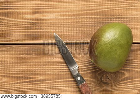 Mango Fruit And A Knife On A Wooden Table. Close Up
