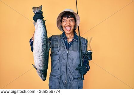 Beautiful brunettte fisher woman holding fishing rod and raw salmon sticking tongue out happy with funny expression.