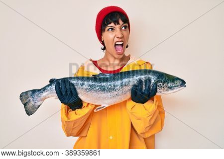 Beautiful brunettte fisher woman wearing raincoat holding fresh salmon angry and mad screaming frustrated and furious, shouting with anger. rage and aggressive concept.