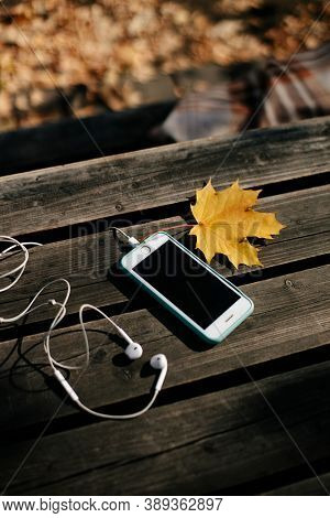 smartphone and headphones on an old wooden table in the park